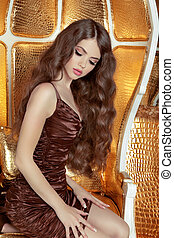 Glamorous fashionable woman with long wavy hair. Model posing on