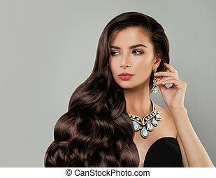 Glamorous jewelry model. Perfect brunette woman with red lips makeup and diamond necklace and earrings portrait