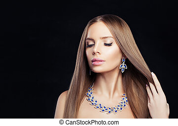 Glamorous jewelry model. Perfect woman with diamond necklace and blue gem earrings portrait