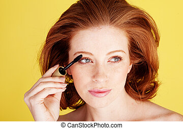 Glamorous Redhead Applying Mascara