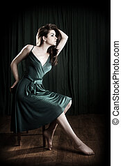 Glamorous Woman - A glamorous young woman sitting on a stool...