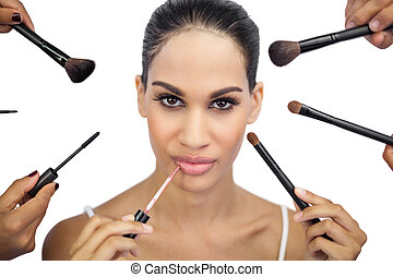 Glamorous woman encircled by make up brushes