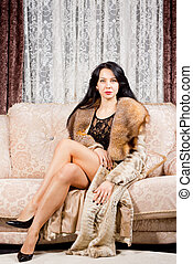Glamorous woman posing in a fur coat