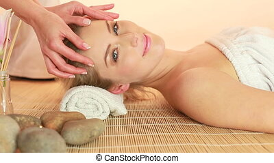 Glamorous Woman Receiving Fingertip Head Massage, lying smiling on mat with masseuse hands only.