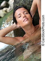 Glamorous woman showering in natural springs