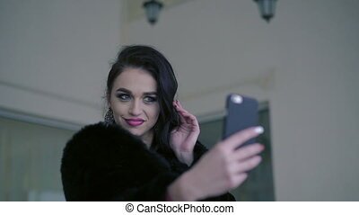 Glamorous woman with seductively lips and eyes posing for selfie