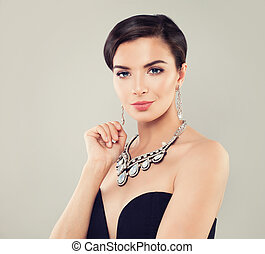 Glamorous woman with short haircut, makeup, diamond necklace and earrings portrait