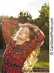 Glamorous young model with blonde wavy hair in fashionable checkered dress