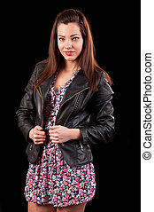Glamorous young woman in black leather jacket on black background