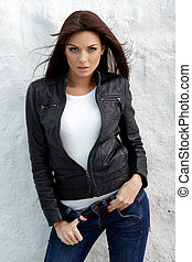 Glamorous young woman in black leather jacket on white ...