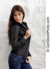 Glamorous young woman in black leather jacket posing near ...