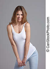 Glamorous young woman in white shirt on gray background