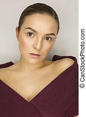 Glamorous young woman with natural makeup posing at grey wall