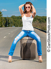 Glamour beautiful girl with a suitcase on the road posing