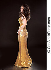 Glamour brunette girl in Fashion golden dress isolated on black background. Elegant lady with Long curly hair, beauty makeup, luxury jewelry.
