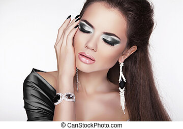 Glamour Fashion Woman Portrait. Elegant girl posing with black makeup and luxury jewelry. Cute female.