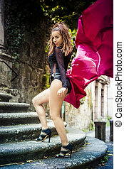 Glamour Girl posing on the streets of the Spanish city of Orense, Galicia. Brunette in tight black dress and big red cloth in the wind