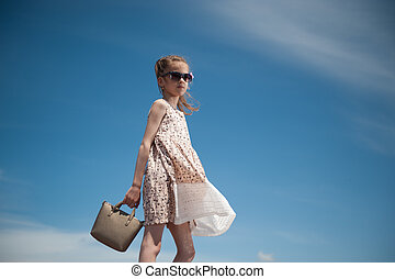 glamour little girl in trendy dress and sunglasses goes on the blue sky background holding a handbag