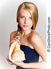 Glamour portrait of beautiful blond woman model with fresh daily makeup and healthy hair. Girl with seashell