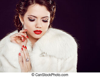 Glamour portrait of beautiful woman model in luxury fur coat over black