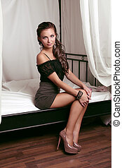 Glamour portrait of beautiful woman model sitting on white bed in interior