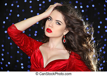 Glamour portrait of beautiful woman model in red with professional makeup and romantic wavy hairstyle around the blue lights on dark holiday background.