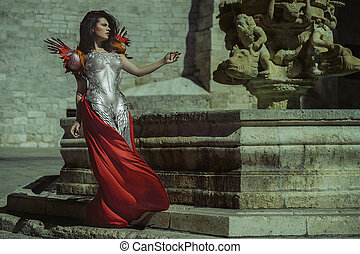 Glamour Queen in silver and gold armor, beautiful brunette woman with long red coat and brown hair