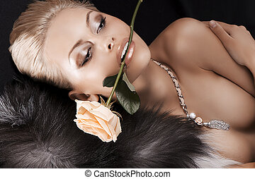 glamour shot of a blonde girl with fur and rose