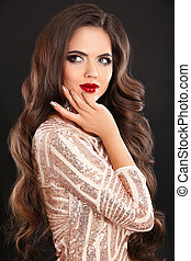 Glamour stunning fashion brunette woman portrait. Long wavy hair style. Red lips beauty Makeup. Healthy shiny hairstyle. Sexy girl model in sequin dress isolated on black background.