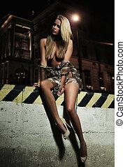 Glamour type photo of cute blonde sitting on the city bridge