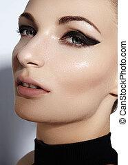 Glamourous closeup female portrait. Fashion eyeliner makeup on model eyes. Cosmetics and make-up. Sexy wild cat style
