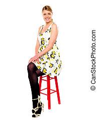 Glamourous woman sitting on stool