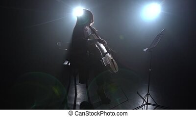Glare from the light in a room girl plays the cello. Silhouette. Black smoke background