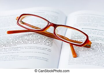 glases on a book - red glases on a open book