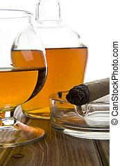 glass and bottle of cognac with a cigar