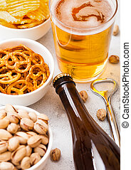 Glass and bottle of craft lager beer with snack and opener on stone kitchen table background. Pretzel and crisps and pistachio in white ceramic bowl.