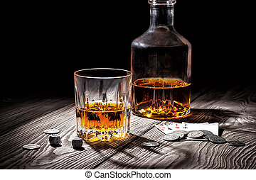 Glass and bottle of whiskey and playing cards and money -...