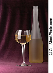 Glass and bottle of white wine on a background of an elegant velveteen material of claret color