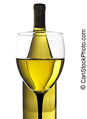 Glass and bottle of white wine on a reflective tabletop