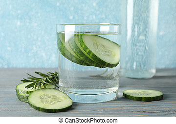 Glass and bottle with cucumber water and slices on wooden table, close up