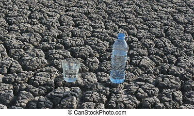 Glass and bottle with water at dry ground