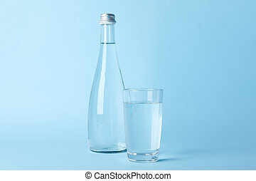 Glass and bottle with water on blue background, space for text