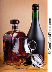 glass and bottles of brandy or cognac on a vintage wooden...