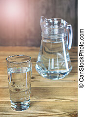 Glass and carafe of the purest water on wooden table