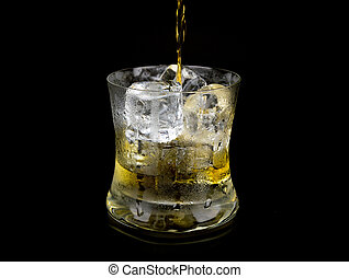 Glass and ice with whiskey on black background.