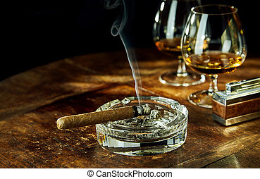 Glass ashtray with smoking cigar by two glasses