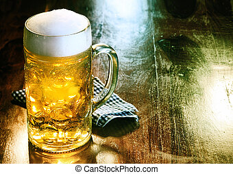 Glass beer mug with golden ale or draft topped with a frothy...