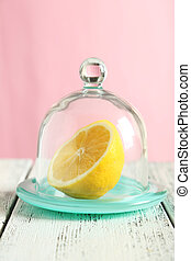 Glass bell jar with lemon on white wooden background