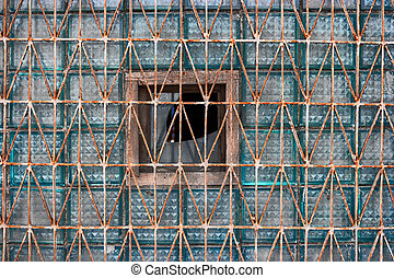 glass block of the old window covered with rusty grid for construction design