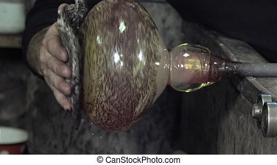 Glass-blower working  - glass blowing and shaping by hand
